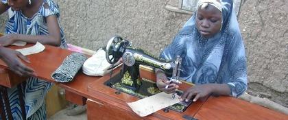 jonge vrouw met hoofddoek achter trapnaaimachine
