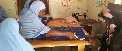 jonge vrouw met hoofddoek knipt grote lap stof op een tafel