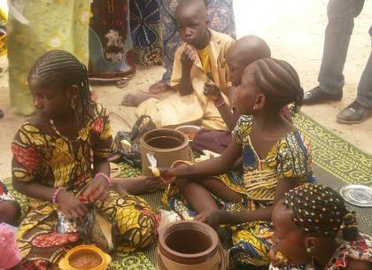 kinderen in kleurrijke kleding, meisjes met ingevlochten haar, zittend op een geweven mat eten uit aarde werken potten